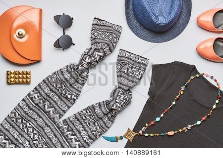 Street style. Fashion summer clothes accessories set. Urban lady, handbag clutch, black top, glamor orange shoes, trendy necklace hat and sunglasses. Bright outfit. Overhead, top view gray background
