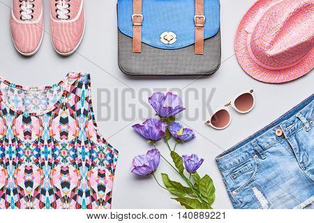 Fashion girl clothes accessories set. Stylish hipster, trendy handbag, top, denim, gumshoes, pink hat, sunglasses and flowers. Bright urban summer outfit. Unusual overhead, top view on gray background