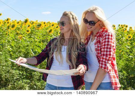 Two girls looking road map standing sunflowers field outdoor, friends near car summer day holiday trip
