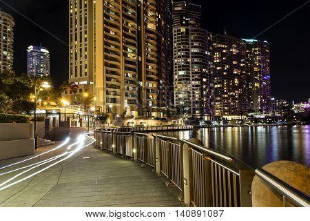 Brisbane cityscape and bike light trails, on the City Reach Boardwalk by night.