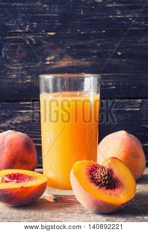 Peach juice in glass with fresh peaches