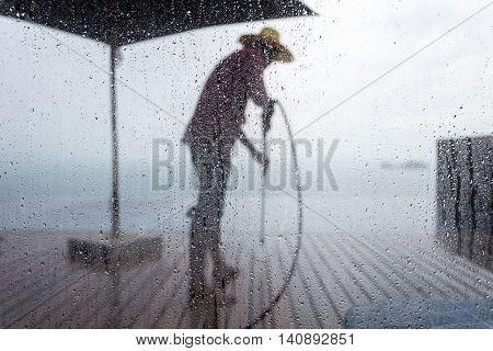 Blurred People Washing Decking By Pressure Wash. Focus On Water Drop