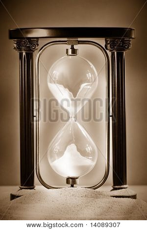 Hourglass resting on beach sand showing sand falling through glass
