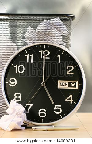 Clock showing time with waste paper basket in background