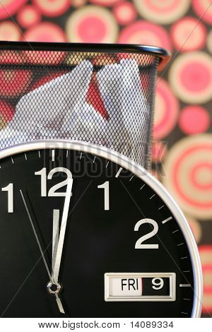 Clock showing time with waste paper basket and retro wallpaper