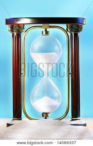 Descansando sobre la arena de la playa de arena de mostrando caer a través del vidrio de reloj de arena