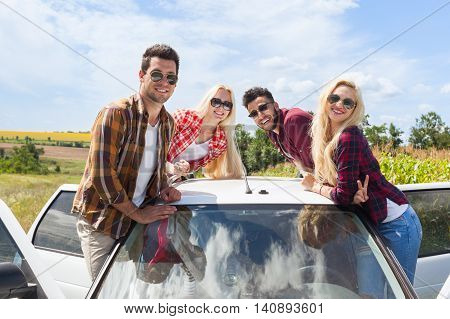 Friends on car roof outdoor countryside people smile summer day trip