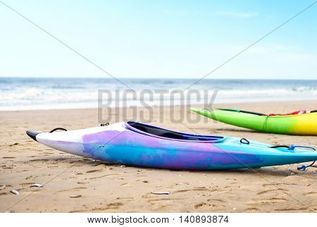 Two multicolored canoes on the beach. Selective focus of canoe boats and view to the turquoise sea and blue sky. Focus on the foreground and copy space.