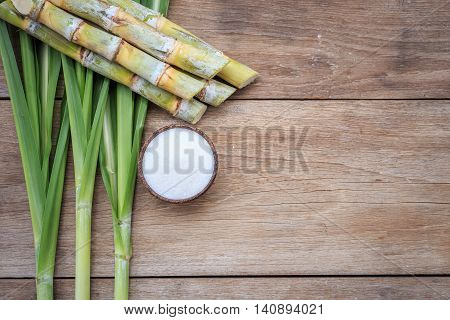 Top View White Sugar And Sugar Cane And Leaf On Wooden