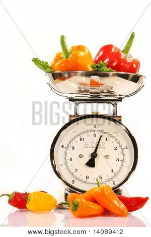 Colored peppers with kitchen food scale on white background