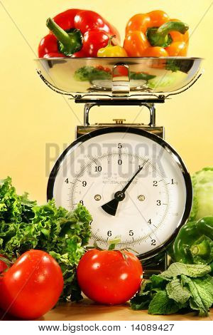 Fresh veggies on kitchen scale with yellow background