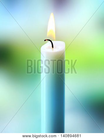 close-up of a burning candle. Selective focus with colored abstract, or defocused background. Candle on a window.