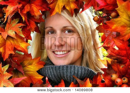 Woman looking through autumn leaves, smiling