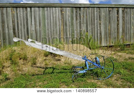 Old two wheeled garden cultivator with wooden handles