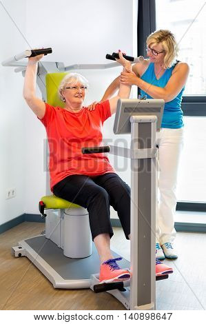 Physical therapist helping senior patient with exercises on machine used to increase shoulder strength