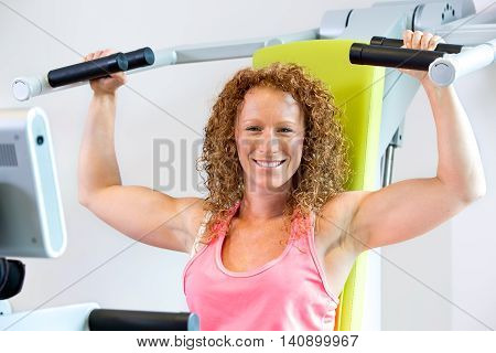 Cheerful Athletic Woman Using Weight Machine