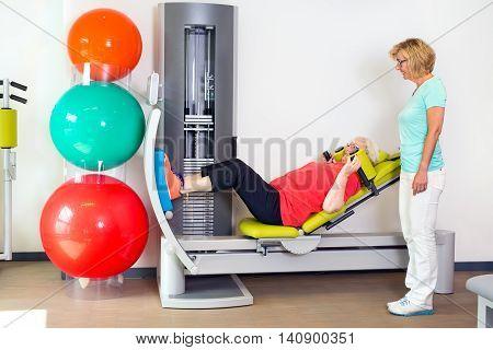 Woman Helping Patient Strengthen Her Legs