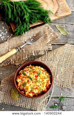Risotto with vegetables in an earthenware bowl, fork, dill sprigs, a cutting board on a wooden table. Rice cooked with tomatoes, garlic and carrots and garnished with dill. Top view