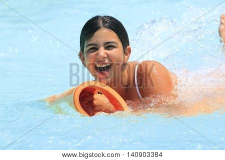 Rhodes Greece-July 30 2016: The young girl in the pool after mat racer slide in Water park. Mat racer slide is very popular