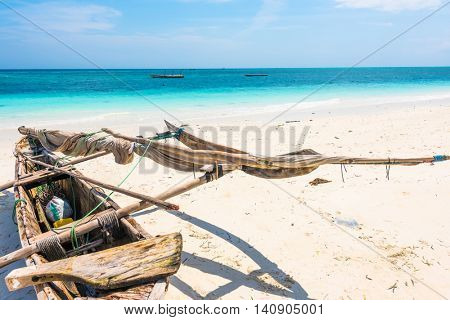 wooden canoe on the shore of Africa with ocean on the background