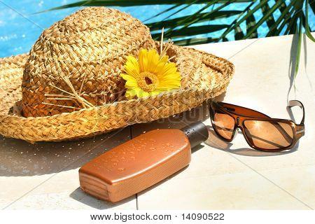 Paja sombrero, gafas y bronceado loción junto a la piscina