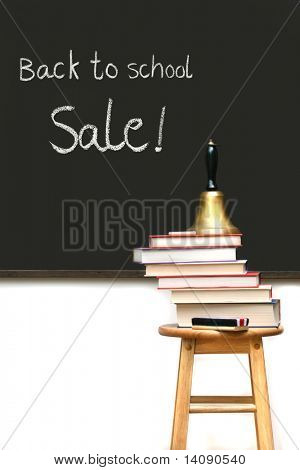 School books on stool with chalkboard