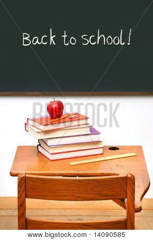 Old school desk with a stack of books and apple