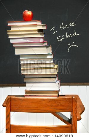 Pila de libros sobre un viejo pupitre con pizarra