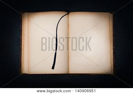 Old book on black stone with empty page for your text