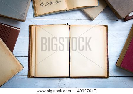 Old books on white wooden desk with empty pages for your text
