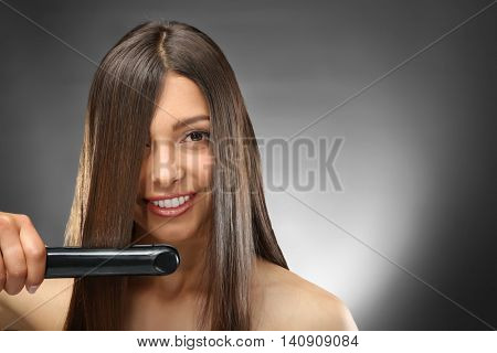 Young beautiful woman straightening hair on dark background