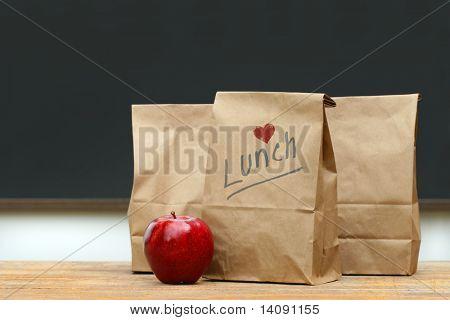Sacos de almoço de papel com maçã vermelha na mesa da escola