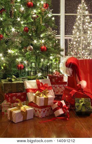 Árbol de Navidad iluminada con un montón de regalos junto a la ventana