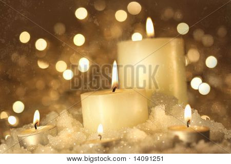 Brightly lit candles in wet snow against sparkly grunge  background