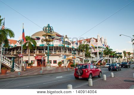 Oranjestad Aruba - December 1 2011: On Main Street Oranjestad stands a colorful mall containing shops and restaurants. Tourists can be seen entering the mall.
