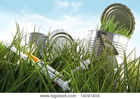 Syringe needles and food cans left in the grass with blue sky