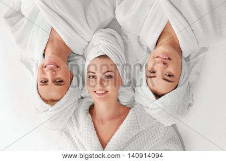 Three beautiful women in dressing gowns, top view
