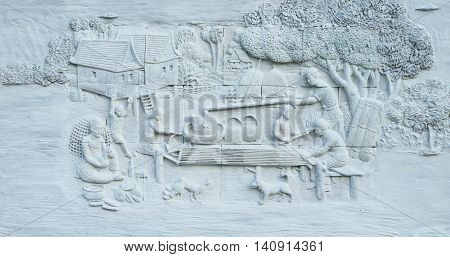 Stone carving and painting of Traditional Thai culture on temple wall