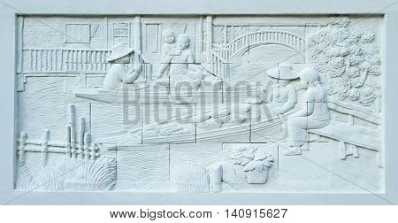 Stone carving of Traditional Thai floating market on temple wall