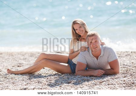 A young couple in love,the guy with the short hair and a girl with long straight blond hair and gray eyes,a beautiful smile and straight white teeth,spend time together,laying on small stones on the beach shore on a background of blue ocean