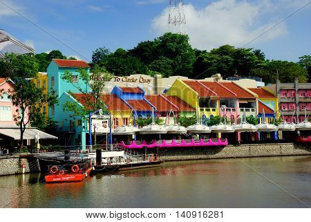 Singapore - December 13 2008: Brightly painted pastel-coloured restored buildings line Clarke Quay on the Singapore River *