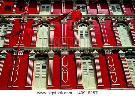 Singapore - December 14 2007: Finely restored late 19th century building painted in bright Chinese red with white wooden shuttered windows on Temple Street in Chinatown