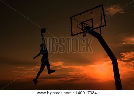 Young man is playing basketball during sunset