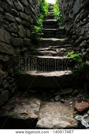 Photo of the Old narrow stone stairs leading up towards the light