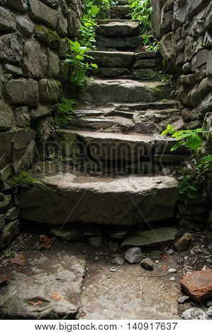 Photo of the Old narrow stone stairs with brick wall. Explore concept