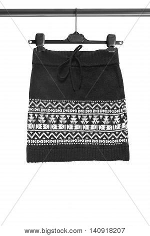 Black knitted skirt on clothes rack isolated over white