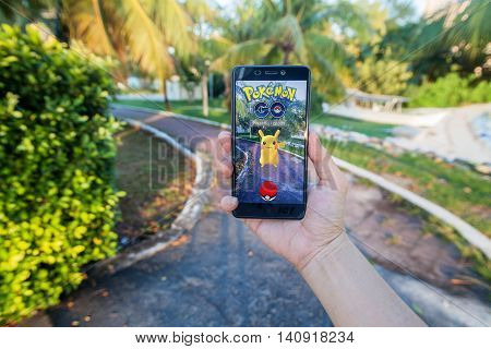 California, United States - July 30, 2016: Close up of a man holding a unbranded smartphone while playing Pokemon Go game with blur background