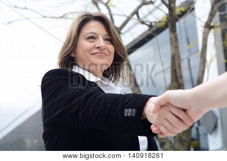 Close up of business woman hand shaking for making a deal. Outdoors.