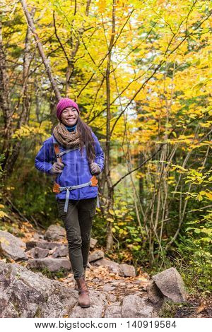Asian woman hiking in autumn forest nature walking on trail path. Hiker girl with backpack hat and jacket on fall adventure travel outdoors relaxing enjoying good weather during hike in cold weather.