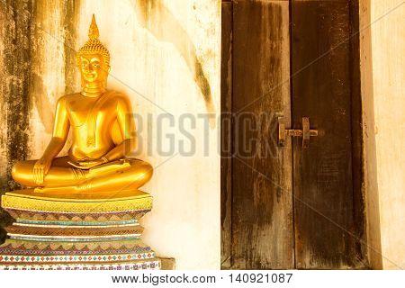 Golden meditating buddha next to close door at Wat Phutthaisawan Ayutthaya Thailand